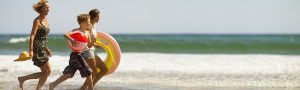 Family running together on the beach with the ocean behind them. Children are carrying a beachball and a round float. The mother is holding onto a straw sun hat.